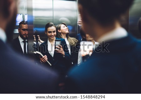 Reflection of group of smiling people in suits carrying documents and taking pictures with smartphone while standing together in elevator cabin at urban office building