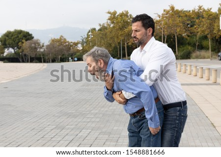Man doing the Heimlich maneuver to an old man with suffocation due to obstruction of the airway with food Royalty-Free Stock Photo #1548881666