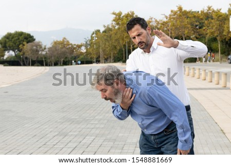 Man doing the Heimlich maneuver to an old man with suffocation due to obstruction of the airway with food #1548881669