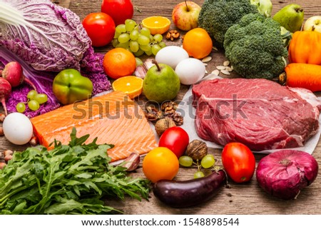 Trending paleo/pegan diet. Healthy balanced food concept. Set of fresh products, raw meat, salmon, vegetables and fruits. Old wooden boards background #1548898544