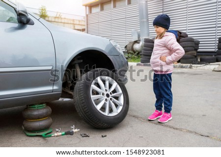 Little girl looks at a broken car in a car service. Auto repair concept. #1548923081