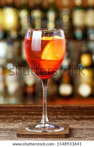 Orange drink based on orange tincture apero, sparkling wine and soda. In a glass a large ice cube and an orange slice #1548933641