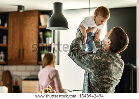 Happy baby boy having fun with his military dad at home. Mother is in the background.  Royalty-Free Stock Photo #1548942494