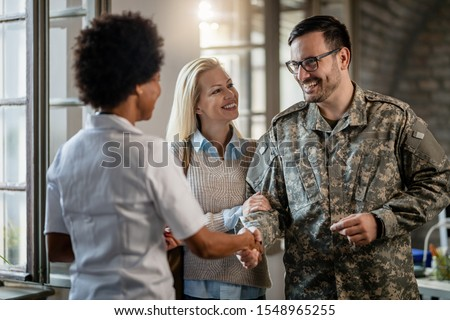 Happy military man shaking hands with female doctor while being with his wife at medical counselling. Royalty-Free Stock Photo #1548965255