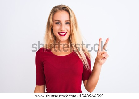 Young beautiful woman wearing red t-shirt standing over isolated white background showing and pointing up with fingers number two while smiling confident and happy. #1548966569