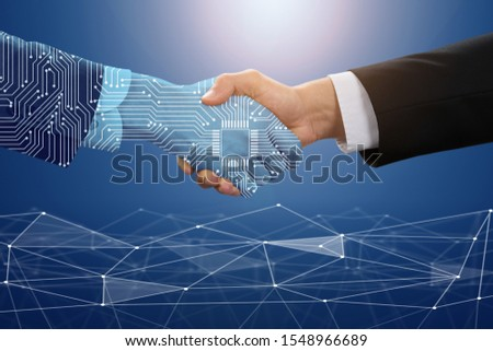Close-up Of Businessman Shaking Hand With Digital Partners Against Blue Technology Background Royalty-Free Stock Photo #1548966689