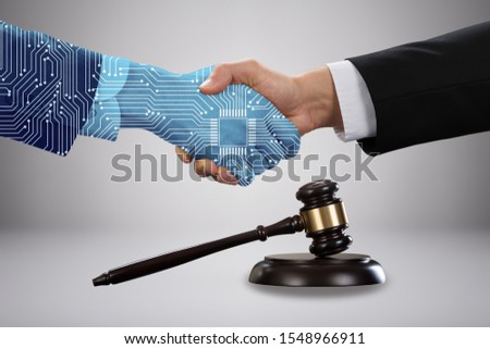 Gavel And Mallet In Front Of Lawyer Shaking Hand With Digital Partners Against Grey Background Royalty-Free Stock Photo #1548966911