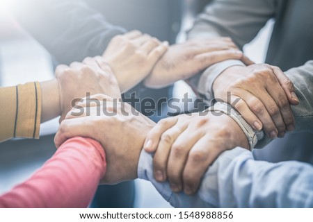 Dramatic moment. A group people hold strong hands. Sign of trust and teamwork. Corporate meeting concept. #1548988856