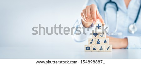 Hand arranging wood block with healthcare medical icon. Health insurance - concept.