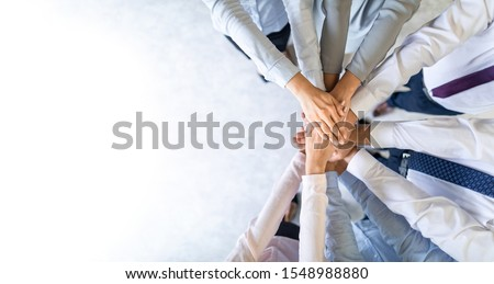 Close up top view of young business people putting their hands together. Stack of hands. Unity and teamwork concept. Royalty-Free Stock Photo #1548988880