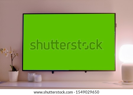 The TV is on the table, the green background on the TV.