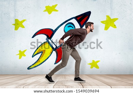 Young man in casual clothes carrying heavy colorful cartoon space rocket on his back on white wall with yellow stars background. Digital art. People and objects. Working hard.