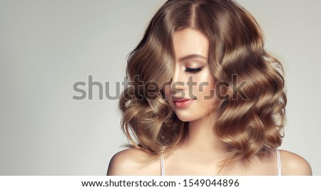 Woman with curly beautiful hair  on gray background. Girl with beauty a pleasant smile. Short wavy  hairstyle