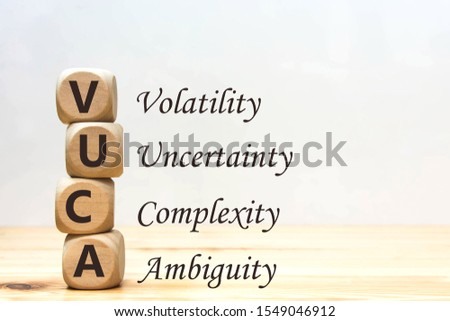Wood cube VUCA alphabet on wooden table wooden white background. Concept abbreviation VUCA block wooden , Volatility, uncertainty, complexity, ambiguity.  #1549046912