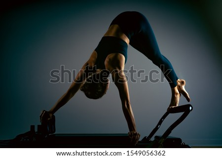 Young girl doing pilates exercises with a reformer bed. Beautiful slim fitness trainer on reformer gray background, low key, art light. Fitness concept #1549056362