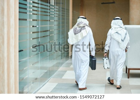 Rear view on sheikh businessmen holding case of money, going to meeting negotiations. In business center #1549072127