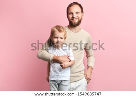 Happy daddy hugging his child, isolated pink background, studio shot, relationship. close up portrait, studio shot. #1549085747