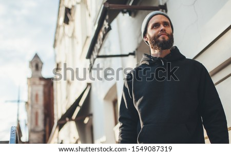 City portrait of handsome hipster man with beard wearing black blank hoodie or hoody and hat with space for your logo or design. Mockup for print