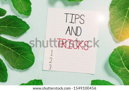 Conceptual hand writing showing Tips And Tricks. Business photo text piece of inside facts specially in betting or investing Leaves surrounding notepaper above empty soft pastel table.