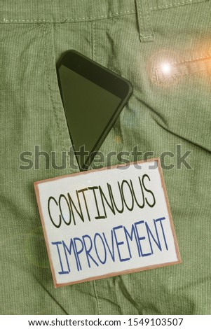 Text sign showing Continuous Improvement. Conceptual photo ongoing effort to improve products or processes Smartphone device inside formal work trousers front pocket near note paper. #1549103507