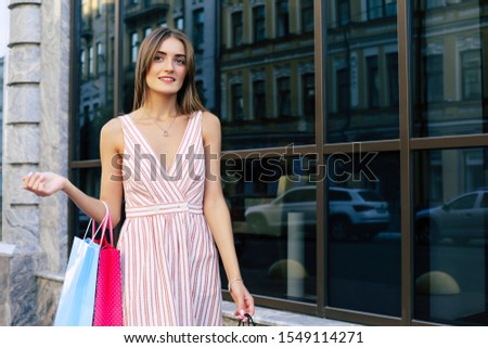 On a sales hunting. Gorgeous girl in a light striped dress is posing at the street with shopping bags, looking aside and smiling. #1549114271