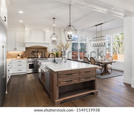 Beautiful kitchen in new traditional style luxury home, with quartz counters, hardwood floors, and stainless steel appliances. Lights are on. Royalty-Free Stock Photo #1549119938