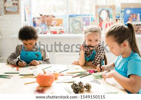 Cute schoolgirl with highlighter by mouth looking at one of classmates drawing face on dry leaf at lesson #1549150115