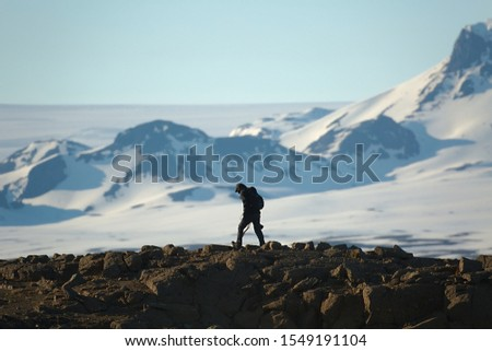 Walking on cliffs in Icelandic Highlands, snowy mountains in the background, hooded man photographer carriing a camera #1549191104
