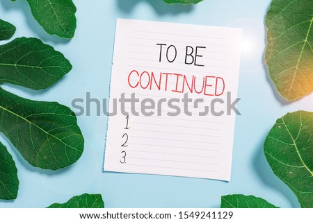 Conceptual hand writing showing To Be Continued. Business photo text indicate that the story continues in the next episode Leaves surrounding notepaper above empty soft pastel table. #1549241129