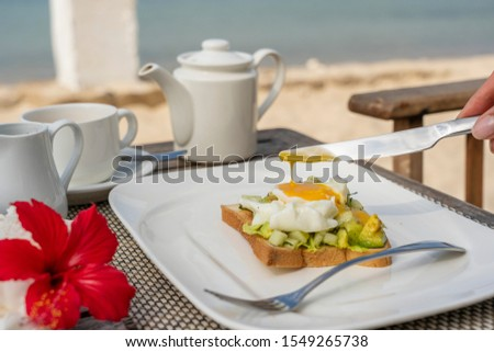Healthy sandwich with avocado, cucumber and poached eggs on table for healthy breakfast on the beach near sea. Food and breakfast concept. Close up #1549265738