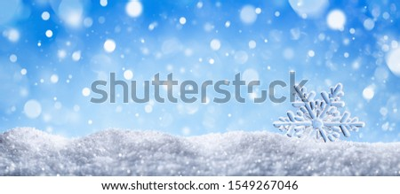 Winter snow background with decorative snowflake against blue sky. Banner format. Beautiful wintertime holiday scene.