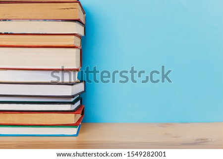 A simple composition of many hardback books, raw books on a wooden table and a bright blue background. Going back to school. Copy space. Education. #1549282001
