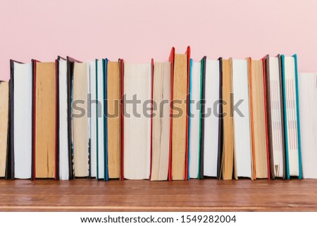 Simple Simple composition of many hardback books, unprocessed books on a wooden table and a pale pink background. back to school. Copy space Education. #1549282004