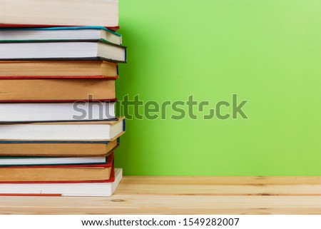Simple Simple composition of many hardback books, unprocessed books on a wooden table and a green background. back to school. Copy space. Education. #1549282007