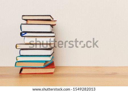 Simple composition of many hardcover books, raw of books on a wooden table and a light background. I'm going back to school. Copy space Education. #1549282013
