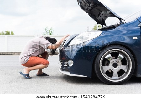 Asian woman 40s alone driver checking a car engine for fix and repair problem with unhappy and dismal between waiting a car mechanic from car engine problem at roadside #1549284776