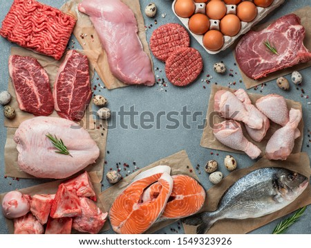 Carnivore diet concept. Raw ingredients for zero carb diet - meat, poultry, fish, seafood, eggs, beef bones for bone broth and copy space in center on gray stone background. Top view or flat lay. Royalty-Free Stock Photo #1549323926