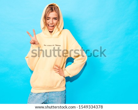 Portrait of young beautiful smiling girl in trendy summer hipster yellow hoodie.Sexy carefree woman posing near blue wall. Positive model having fun.Winks and shows peace sign #1549334378