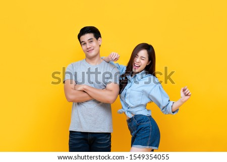 Lovely young smiling Asian couple in casual clothes isolated on yellow backgound #1549354055