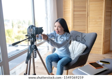 Excited lifestyle blogger. Excited lifestyle blogger holding camera before making video about gadgets #1549369259