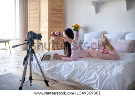 Lifestyle blogger. Lifestyle blogger working on laptop and filming blog while lying in bed #1549369301