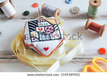 Handmade and needlework. Handmade pin cushion with a simple ornament and sewing supplies on the white background. Top view #1549389902