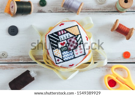 Handmade and needlework. Handmade pin cushion with a simple ornament and a pair of scissors on a white table. Sewing supplies in the background. Top view #1549389929