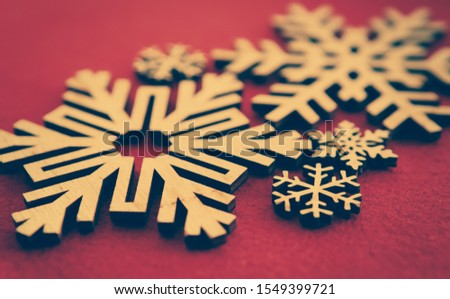 Handmade snowflakes for winter holidays.Merry Christmas and Happy New Year home decor.Hand made crafts for presents and decoration edited with vintage film filter,photo on red background