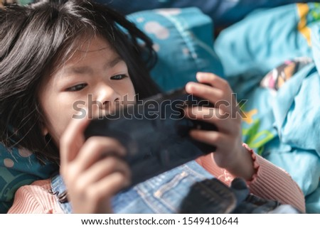 Little cute girl playing games on her smathphone on morning time after wake up, Selective focus, Children's Smartphone Addiction problem.