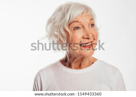 Portrait of happy, cheerful and positive old woman posing on camera alone. Amazing and beautiful smile. Close up. Wear white shirt. Stand alone. Isolated over white background
