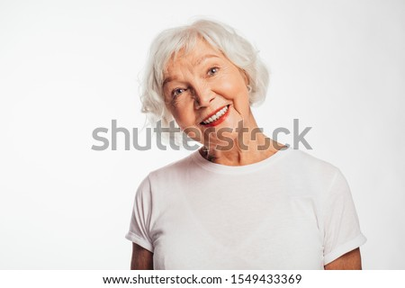 Lovely, cheerful and positive old woman on picture. Smile and look up. Dreaming about something. Wear white shirt. Elder with gray hair on picture. Isolated over white background