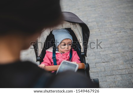 mother carries a baby in a stroller regularly using a mobile phone without paying the child any attention. The problem of young mothers dependence on gadgets #1549467926