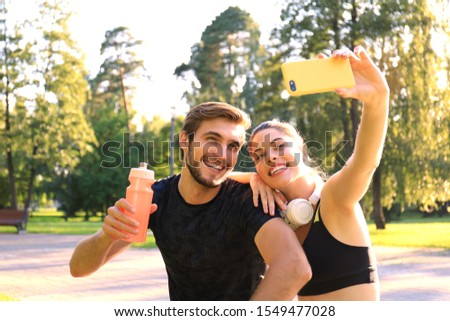 Young sporty couple in sportswear sitting on parapet in urban park and taking selfie after workout on summer sunny day. #1549477028