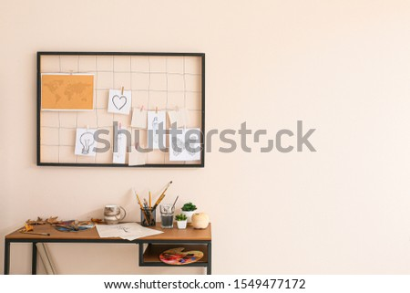 Comfortable workplace with mood board near light wall #1549477172